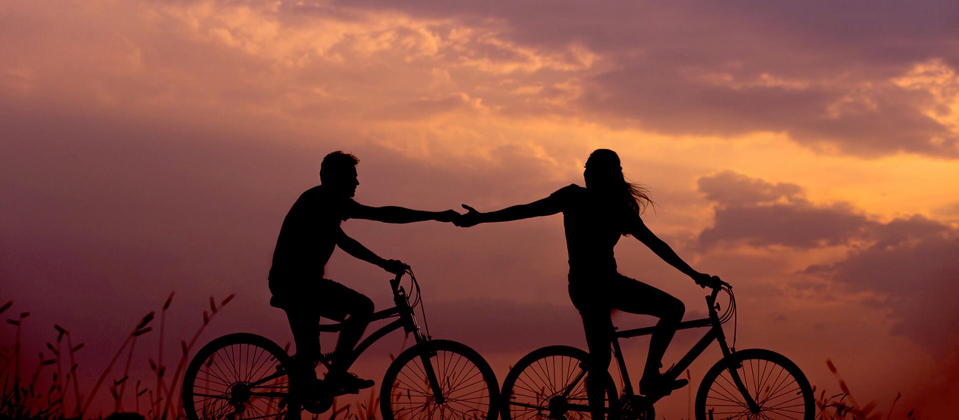 Couple d'amoureux en vélo au coucher de soleil